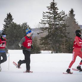 Les athlètes compétitionnent en plein air dans une course serrée de raquettes.
