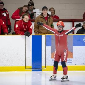 Un patineur de vitesse lève les bras et se prépare à participer aux Jeux olympiques spéciaux.