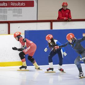 Des athlètes s'affrontent dans une course serrée de patinage de vitesse.