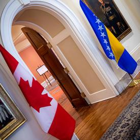 The Canadian and Bosnia and Herzegovina flags are on either side of a door.