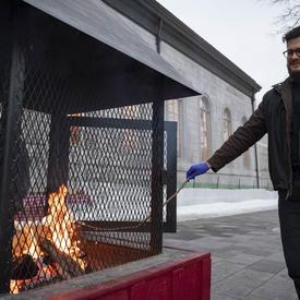 Une photo d'un homme faisant rôtir une guimauve sur un feu à Rideau Hall.