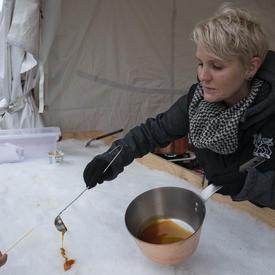 Un employé de Rideau Hall verse de la tire d'érable sur de la glace pendant la réception hivernale pour le corps diplomatique.