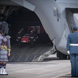 CAF members, including a bagpiper watch as a coffin, carried by CAF members, is taken off a plane.