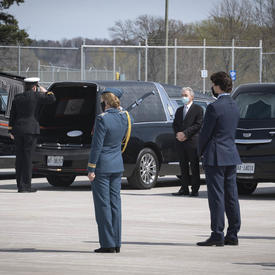 The Governor General salutes a coffin as it is placed in a hearse. The Prime Minister is standing behind her.