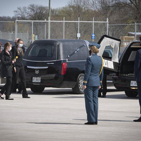 Family members of the deceased walk towards the hearse. The Governor General and the Prime Minister are standing near the hearse.