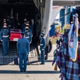 Le cercueil de la capitaine Jennifer Casey est transporté hors de l'avion par des membres des Forces armées canadiennes. Un joueur de cornemuse est au premier plan de la photo.