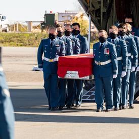 Le cercueil de la capitaine Jennifer Casey est transporté hors de l'avion par des membres des Forces armées canadiennes.