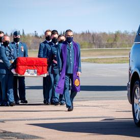 Le cercueil de la capitaine Jennifer Casey est transporté par des membres des forces armées canadiennes vers le corbillard. Le chapelain est devant le cercueil,
