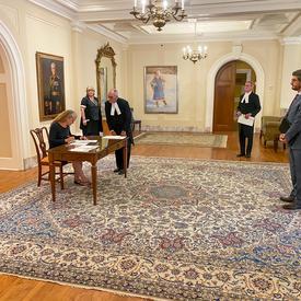 Vue de côté. Assise sur une chaise de bois, à une table de bois, la gouverneure générale signe un document.