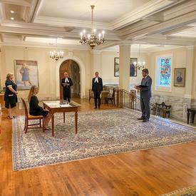 Vue de côté de la gouverneure générale, assise à une table. Derrière elle se trouve un drapeau du Canada. Devant elle, un homme en complet-cravate tient un document.