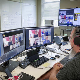 A man with a head set is sitting at a computer, looking at two large screens in front of him. A virtual conversation with 4 participants seems to be taking place.