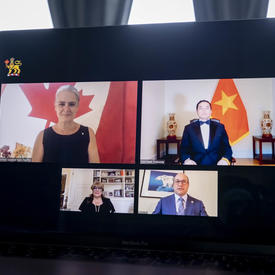A laptop is opened in front of a large window with grey-blue draps. On the screen, we see 4 people, 2 women and 2 men, in 4 different rectangles. The flag of Vietnam in behind one of the men.