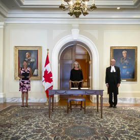 Five people standing in front of a pastel yellow wall. A table is in front of the person standing in the middle. A Canadian flag is placed to her right.