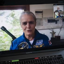 Une femme en combinaison de vol spatial bleue est présentée sur un écran d'ordinateur portable ouvert.