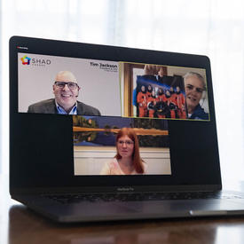 An open laptop is shown with the screen divided in three. On the top left is a man wearing a gray suit; on the top right is a woman holding up a photo of 8 astronauts. On the bottom is a young girl.