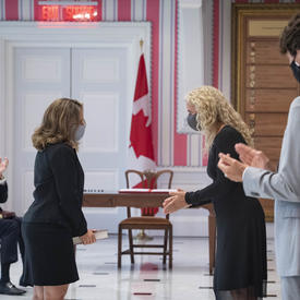 A woman is standing facing Governor General Payette and Prime Minister Trudeau who are applauding.