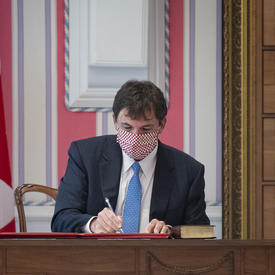 A man is seated at a desk to the right of a large Canadian flag. He is signing a document.