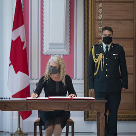 A woman is seated at a desk between a large Canadian flag and a soldier in dress uniform. She is signing a document.