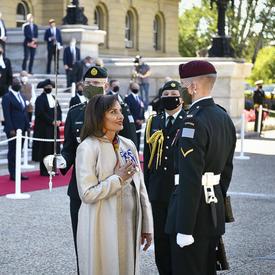 Une femme vêtue de blanc se tient devant un soldat en tenue de service. L'uniforme de Hius comporte un chevron au bras gauche. La femme a la main droite pressée sur sa poitrine et elle sourit.