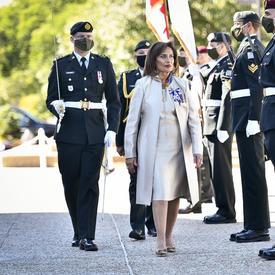 Une femme habillée en blanc est accompagnée d'un militaire en tenue de service portant une épée. Ils passent devant une ligne droite de militaires au garde-à-vous.