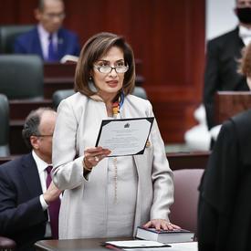 Une femme vêtue de blanc lit à haute voix un document qu'elle tient dans ses mains. Elle fait la lecture à une femme portant la robe de juge qui se tient en face d'elle, à une table de taille moyenne.