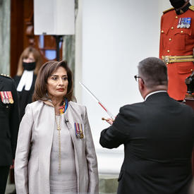 A man in a dark suit touches the shoulder of a woman dressed in white with a metal sword. Standing behind the woman are a military member in service dress and three people dressed in black ceremonial attire. One is holding a black staff with metal trim.