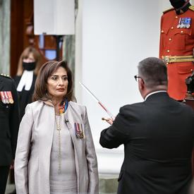 Un homme en costume sombre touche l'épaule d'une femme vêtue de blanc avec une épée en métal. Derrière la femme se tiennent un militaire en tenue de service et trois personnes en tenue de cérémonie noire. L'un d'eux tient un bâton noir avec une garniture