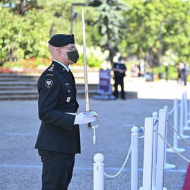 A military member in service dress holds a sword in front of him. A woman dressed in white is standing in front of him.