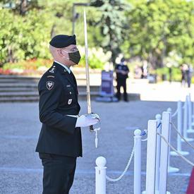 Un militaire en tenue de service tient une épée devant lui. Une femme vêtue de blanc se tient devant lui.