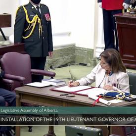 Une femme vêtue de blanc est assise à une table. Elle signe un document. Un homme en costume sombre et un militaire en tenue de service la regardent.