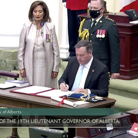 Un homme en costume sombre est assis à une table. Il signe un document. Un autre homme en costume sombre, une femme en blanc et un militaire en tenue de service le regardent.