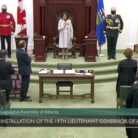 Une femme vêtue de blanc se tient devant un trône en bois flanqué de trois militaires. Elle fait face à une salle remplie de spectateurs qui l'applaudissent.