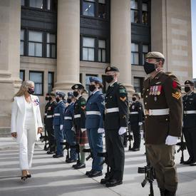 Une femme vêtue de blanc passe devant plusieurs militaires qui se tiennent au garde-à-vous. Certains sont vêtus de vert, d'autres sont habillés de noir. Un homme en uniforme se trouve également à la droite de la femme. Tous portent un masque.