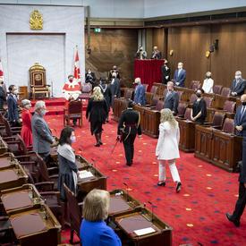 Un cortège de personnes marche sur un tapis rouge vers l'avant d'une grande salle au tapis rouge. Trois des personnes sont vêtues de noir. Une femme est vêtue de blanc. Il y a un trône flanqué de deux drapeaux du Canada à l'avant de la salle.