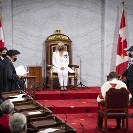 Une femme vêtue d'un costume blanc est assise sur un trône. Il y a des drapeaux du Canada de chaque côté de la plate-forme. Un homme assis sur une chaise lui fait face. Il porte un manteau rouge et blanc.