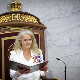 Une femme vêtue d'un costume blanc est assise dans un trône et tient ouvert un porte-document noir. De chaque côté d'elle se trouvent de petits microphones.