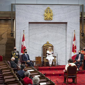 Une femme en costume blanc est assise sur un trône et tient un porte-document noir. Un homme est assis face à elle sur un tapis rouge. On peut également voir d'autres personnes dans le public, assises.