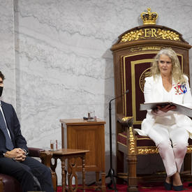 Une femme vêtue d'un costume blanc est assise sur un trône et tient ouvert un porte-document noir. Il y a une petite table en bois à sa droite. Il y a également un homme à sa droite. Il est vêtu d'un costume noir avec une cravate bleu marine.