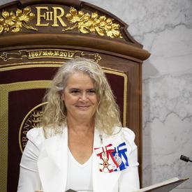 Une femme en chemise blanche et veste blanche sourit. Sa veste est décorée de médailles. Elle est assise sur un trône, tenant un porte-document noir.