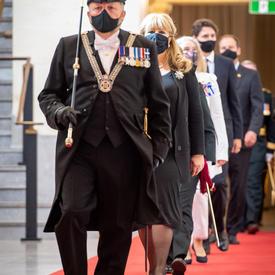 Une file de personnes marchent vers la caméra sur un tapis rouge. L'homme qui dirige le groupe porte un uniforme noir décoré, avec un bâton noir et doré. Il porte également un chapeau noir et un masque noir.