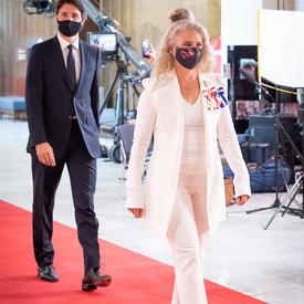 Une femme vêtue en costume-pantalon blanc marche sur un tapis rouge. Elle porte des talons noirs et un masque noir. Un homme marche derrière elle dans un costume sombre et porte également un masque.