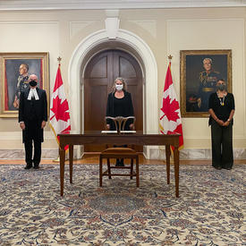 Four people wearing face masks are standing near the back of the room. There is a wooden table and chair in front of the woman in the centre of the picture. There are two Canadian flags on either side of her.