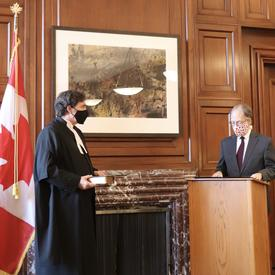 Chief Justice Richard Wagner holding a book. Ian Shugart - clerk of the Privy Council of Canada - stands a podium.