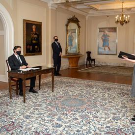 L'administrateur est assis à une table. Le secrétaire se tient à sa gauche. On distingue le profil de côté de deux personnes qui se tiennent debout et qui regardent en direction de l'administrateur.