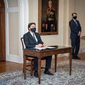 L'administrateur est assis à une table. Le secrétaire se tient à sa gauche.