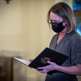 Une femme lit un document. Elle porte un masque noir.