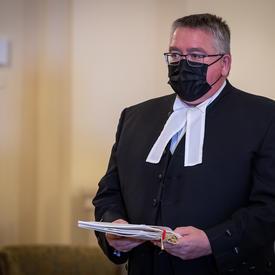 Un homme, portant une tenue noire avec un col blanc, tient des documents.
