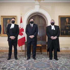 L'administrateur se tient entre quatre personnes. Toutes les personnes portent des masques. Un drapeax du Canada se trouve à l'arrière-plan.
