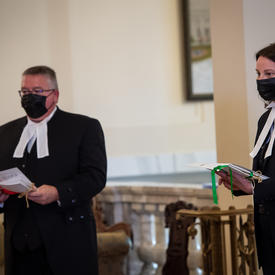 Two people, both dressed in black with white collars, each holding documents.
