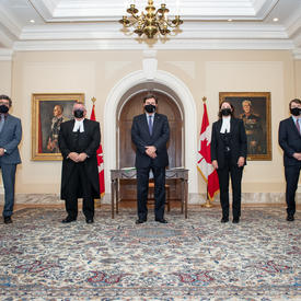 The Administrator flanked on either side by two people. All wearing masks. Two Canadian flags in the background.